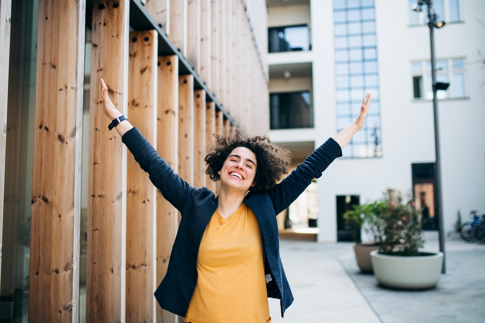 A young businesswoman standing outdoors, expressing excitement