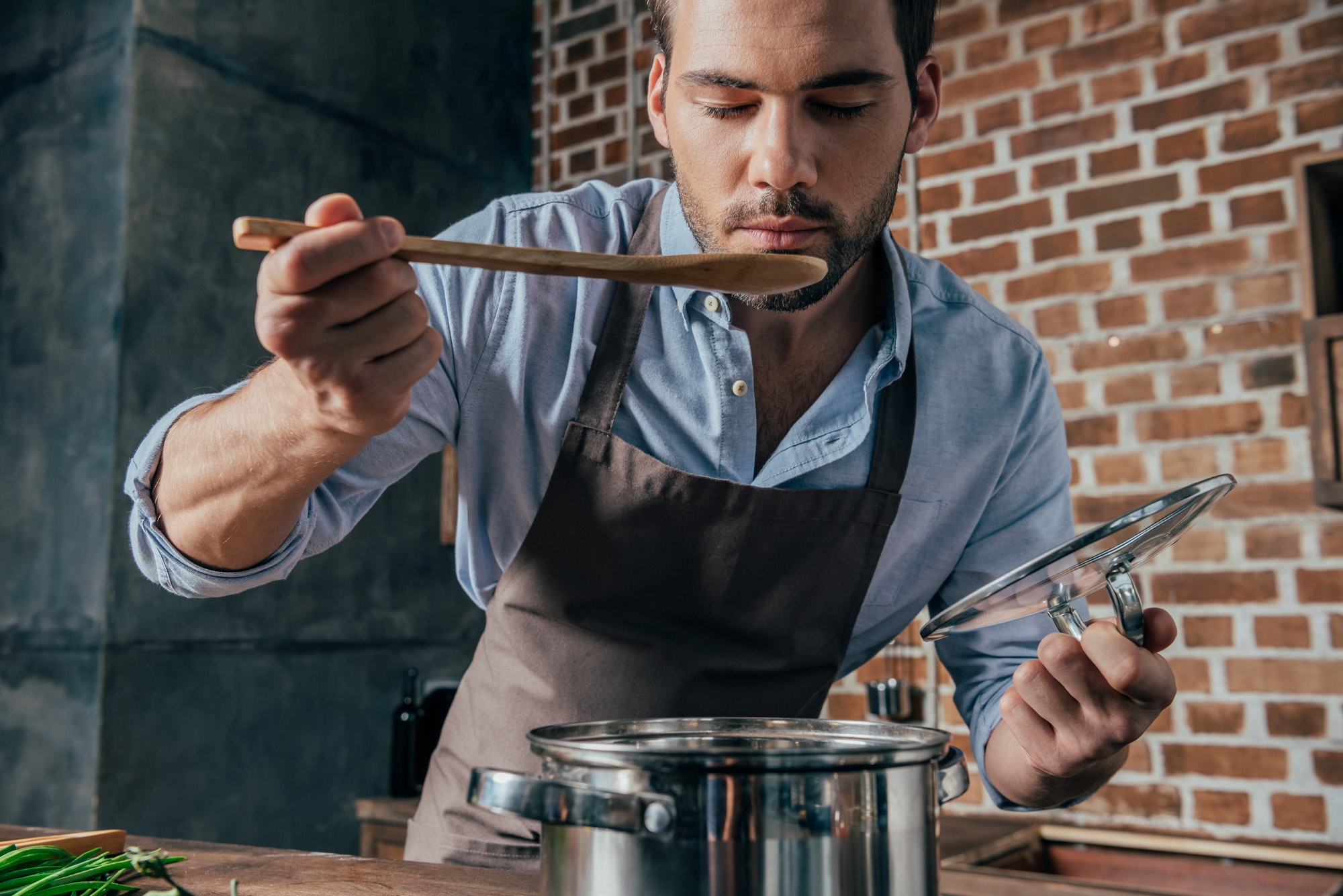 stylish young man with apron cooking soup